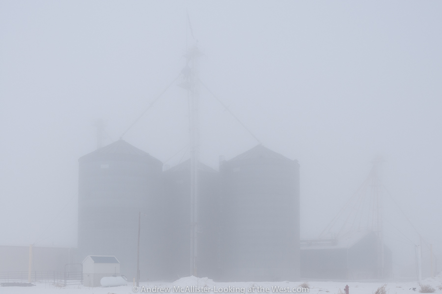 Photograph of grain silos in dense fog.