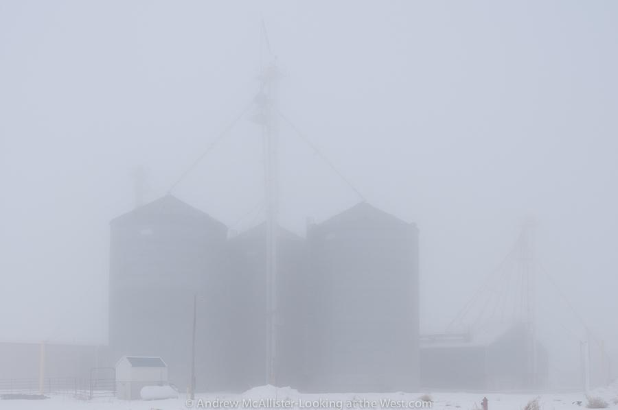 Photograph of grain silos in dense fog.